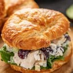 Close up of Chicken Salad in a croissant sandwich sitting on a cutting board.