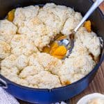 Dutch Oven Peach Cobbler in a blue dutch oven, a scoop has been taken out and put in a bowl