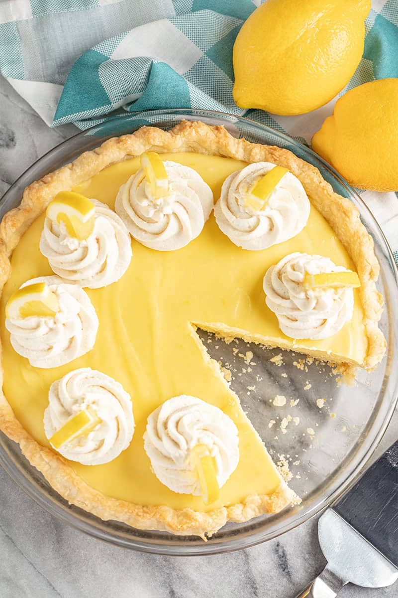 Old Fashioned Creamy Lemon Pie topped with dollops of stabilized whipped cream and lemon wedges