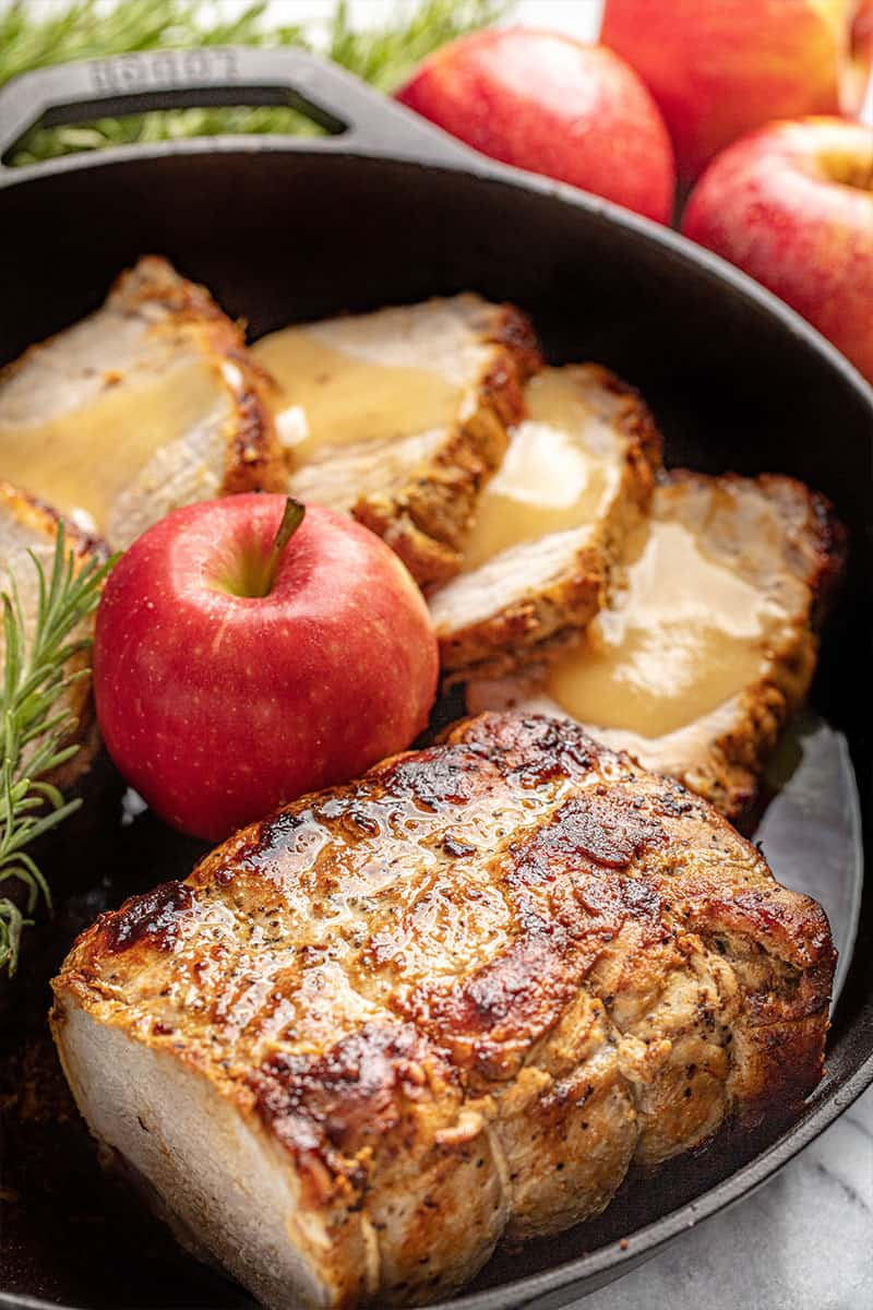 Apple Glazed Roasted Pork Loin in a skillet with an apple.