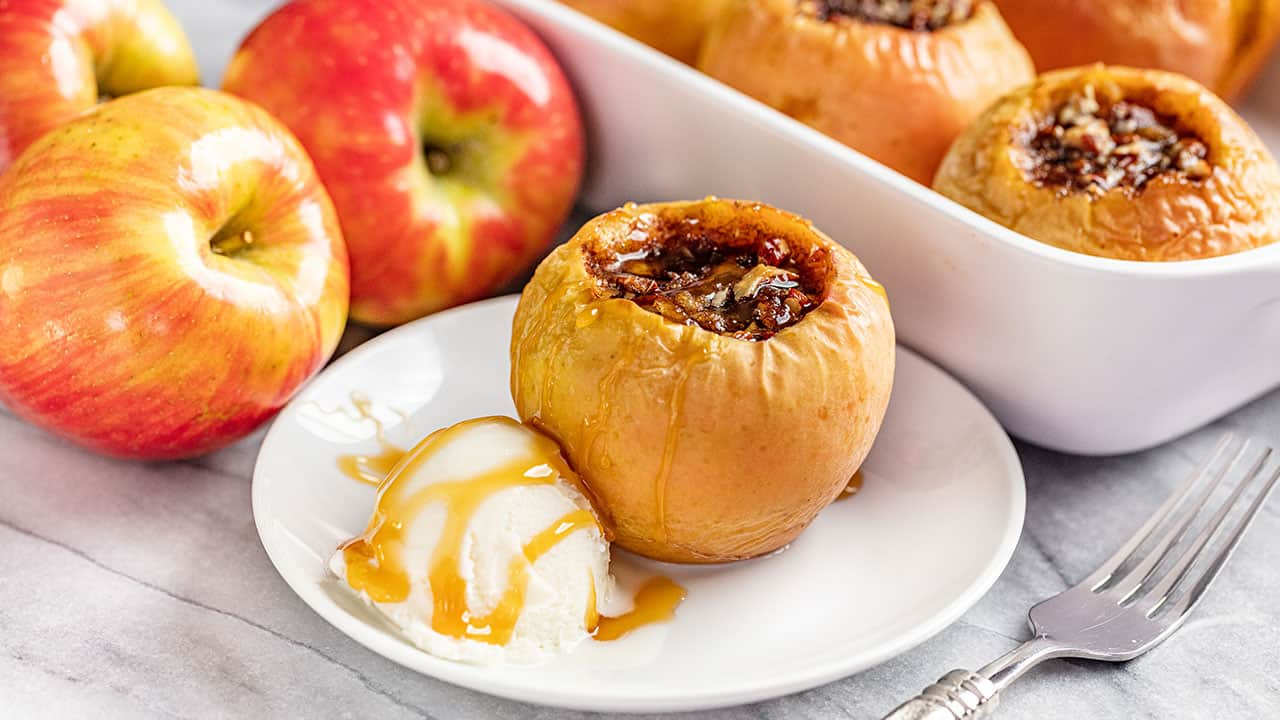 Baked Apple with a scoop of Ice Cream with a white dish full of baked apples in the background.