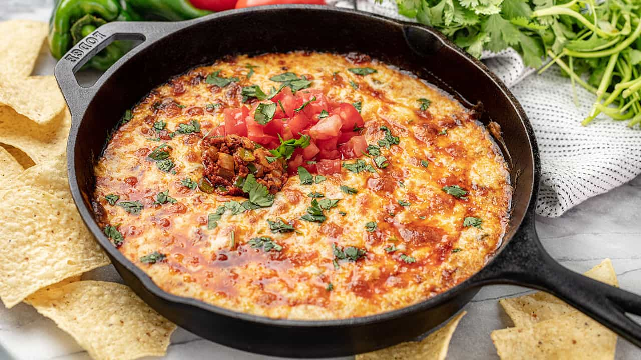 Queso Fundido in a skillet with bubbly cheese and topped with chorizo, fresh chopped roma tomato and cilantro