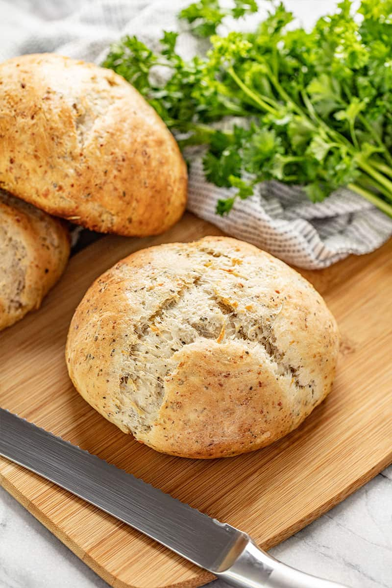 Rustic Garlic Parmesan Herb Bread on a cutting board with a bread knife by it.