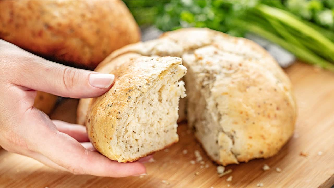 Hand holding a slice of rustic garlic parmesan herb bread with the rest of the loaf of bread in the background.