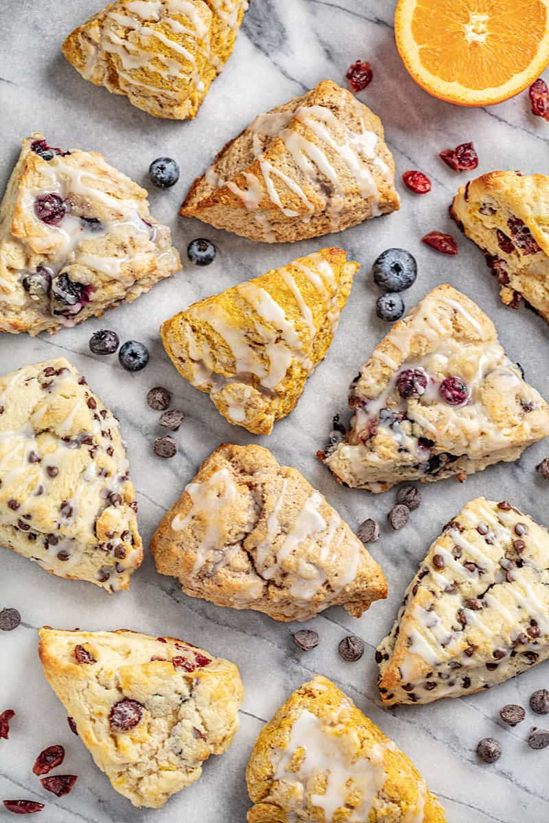 Bird's eye view of British Scones in various flavors. Chocolate Chip scones, Pumpkin Scones, Cranberry Orange Scones, Blueberry Scones, and Cinnamon Scones