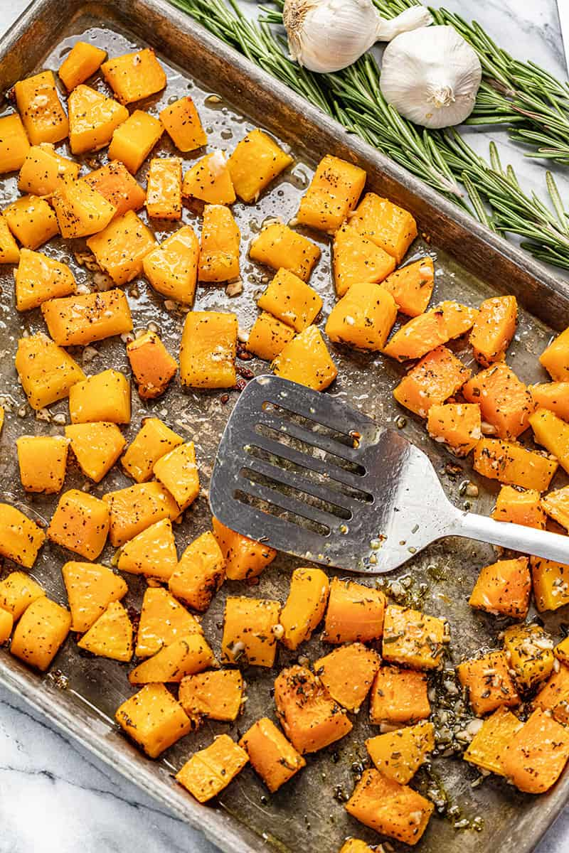 Bird's eye view of butternut squash on a baking sheet with a spatula on it.