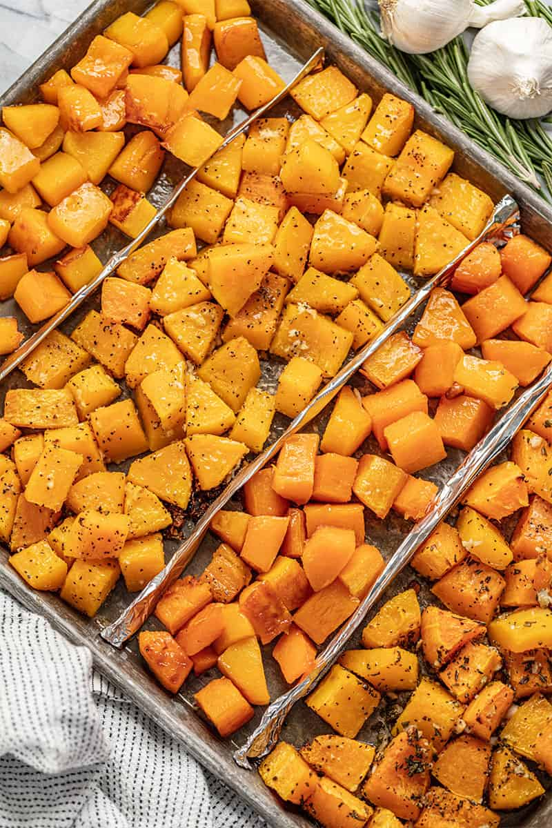 Bird's eye view of four different flavors of Roasted Butternut Squash on a baking sheet.