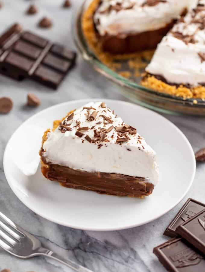Slice of chocolate cream pie on a plate with the whole pie in the background