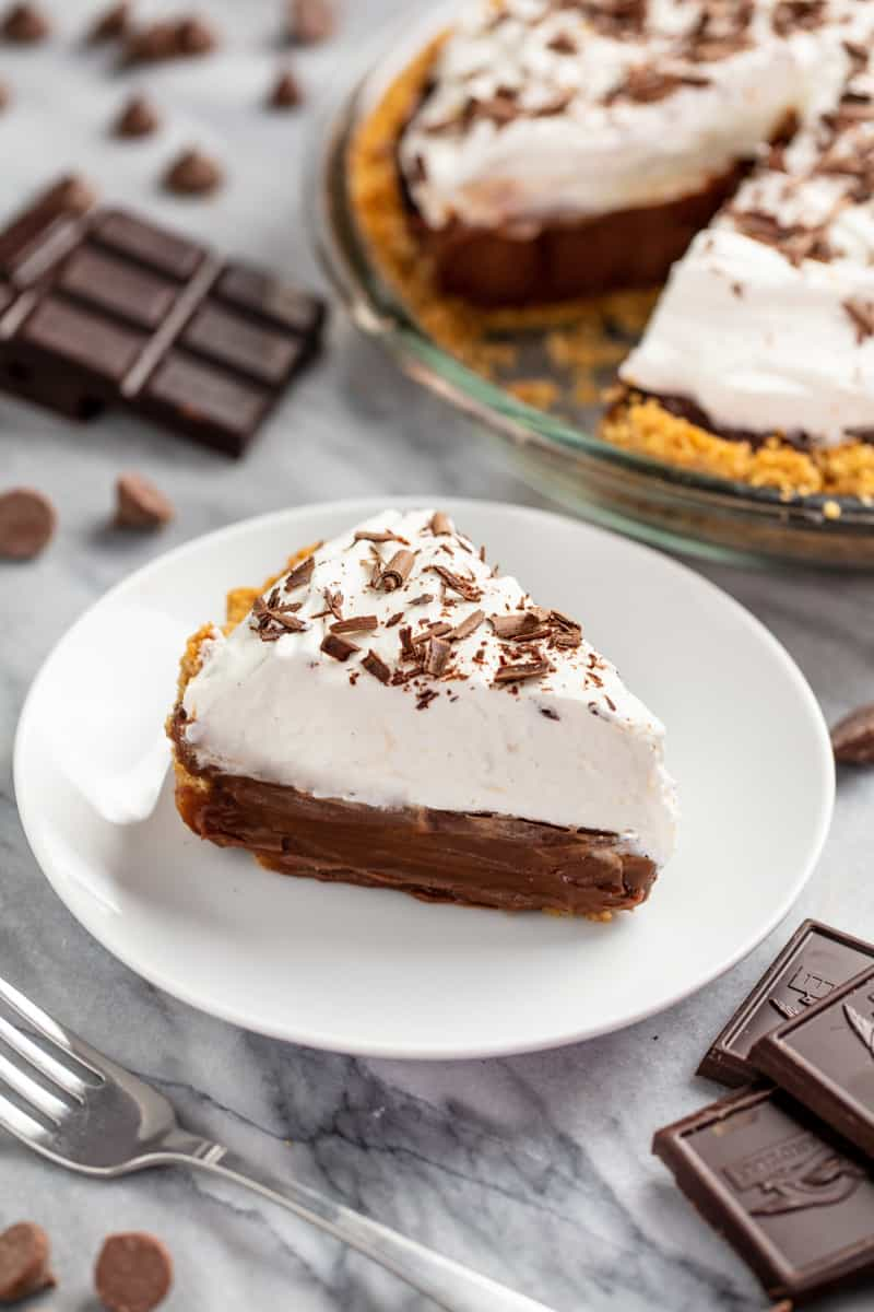 Slice of chocolate cream pie on a white plate with a chocolate pie in the background.