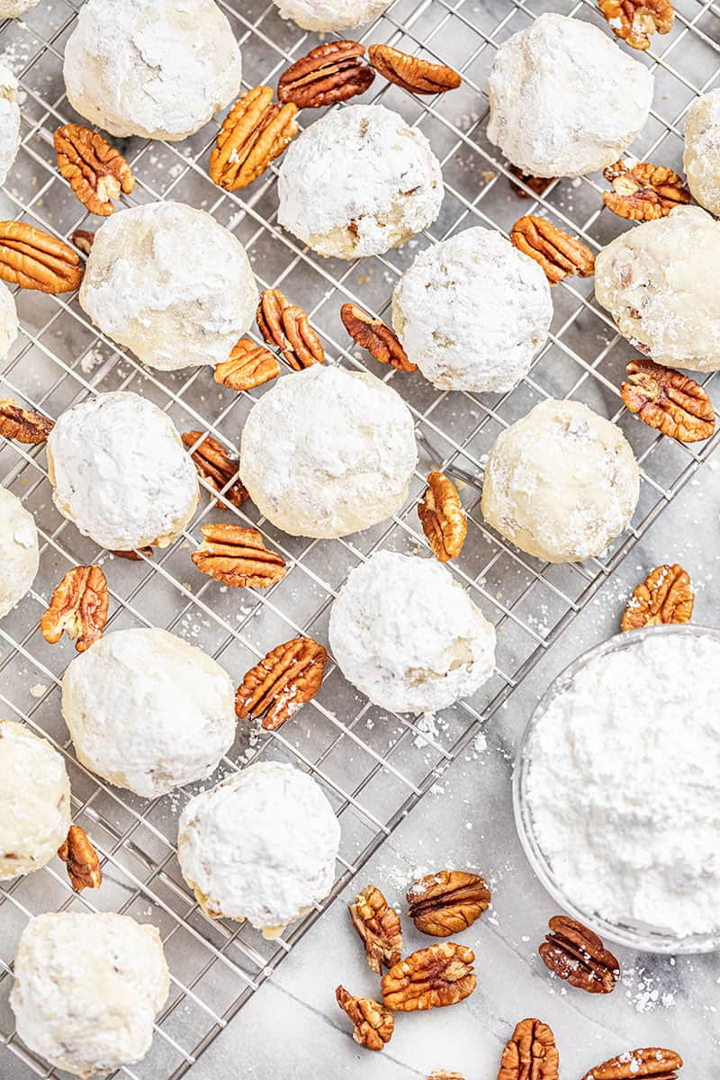 Pecan Sandies on a wire cooling rack with pecans and a bowl of powdered sugar