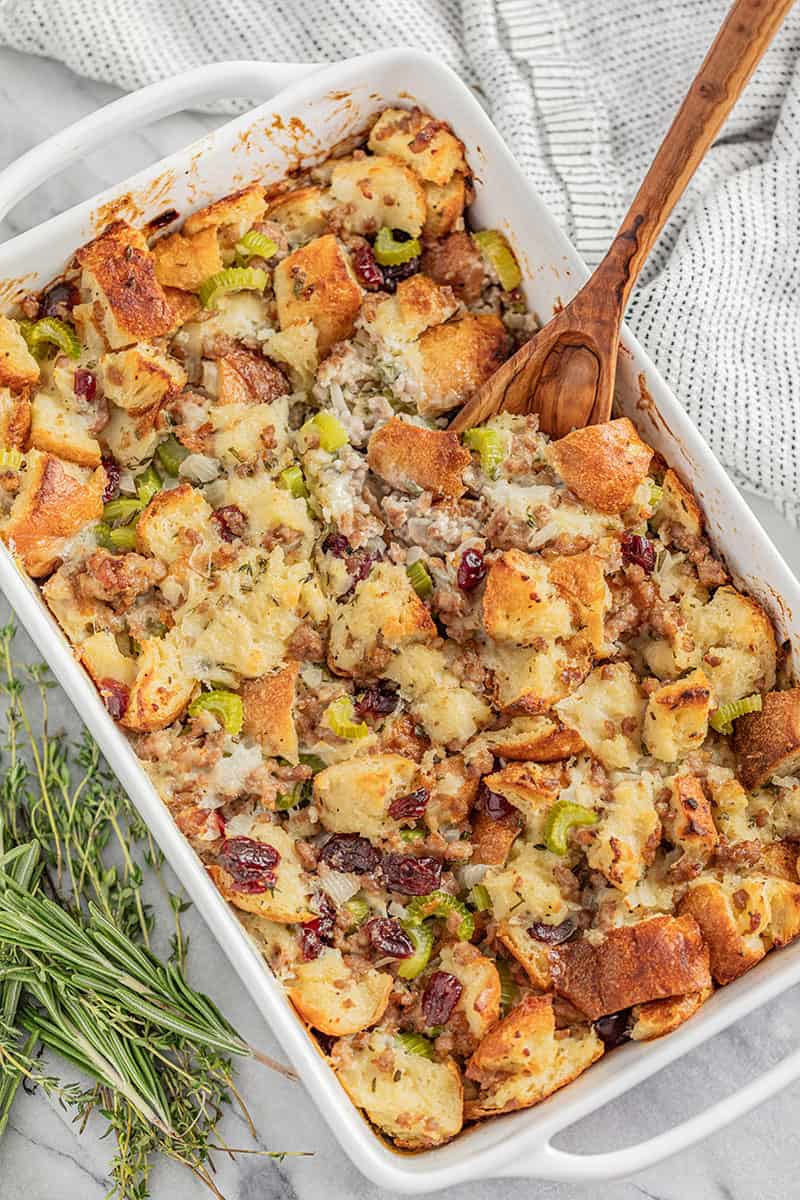 Bird's eye view Sausage Stuffing in a white dish with a wooden spoon in it.