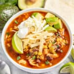 Bowl of chicken tortilla soup topped with cheese, avocado, tortilla strips, lime, and cilantro