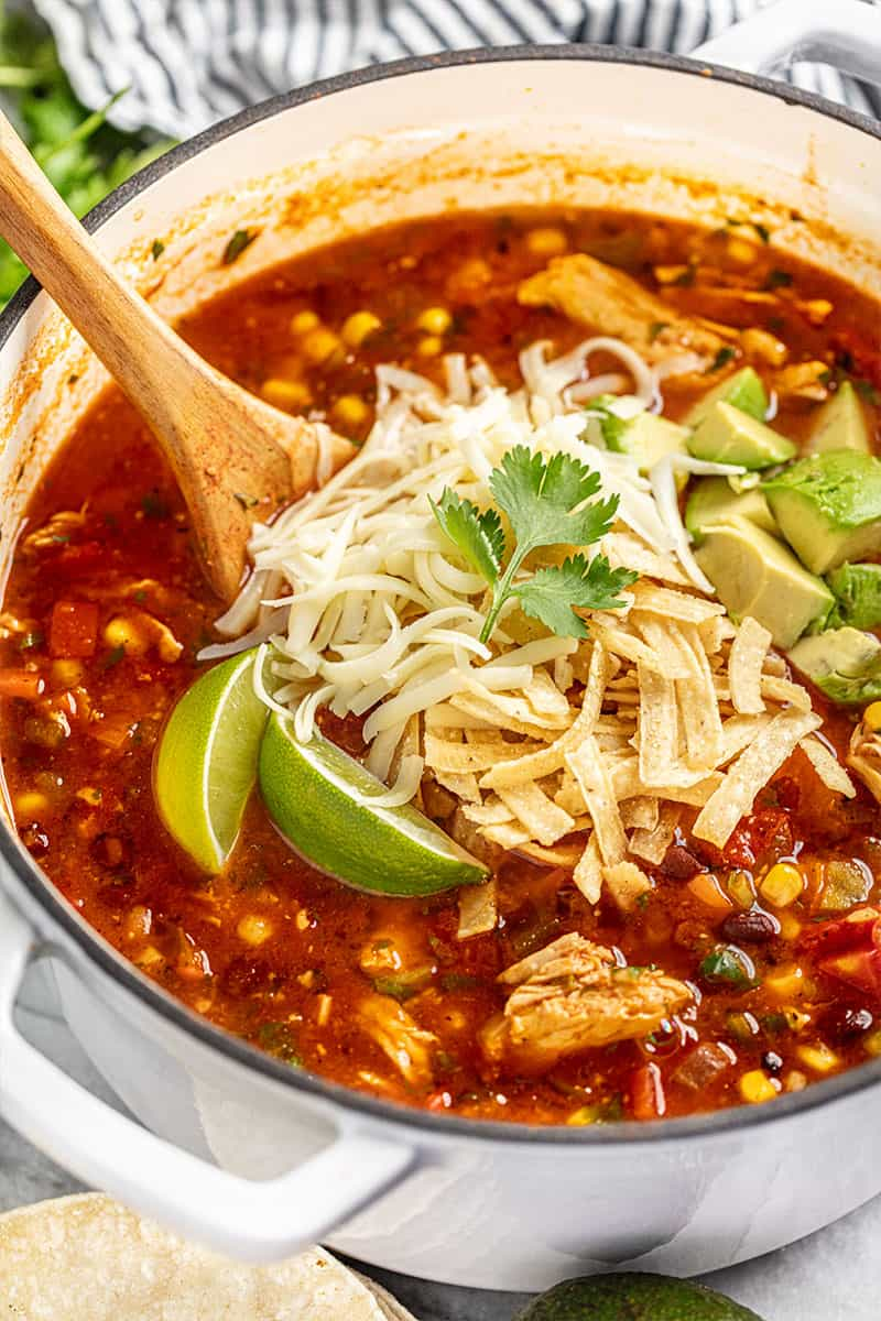 Pot of chicken tortilla soup topped with cheese, avocado, tortilla strips, lime, and cilantro