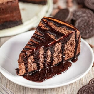 Chocolate Cheesecake on a white plate surrounded by oreos