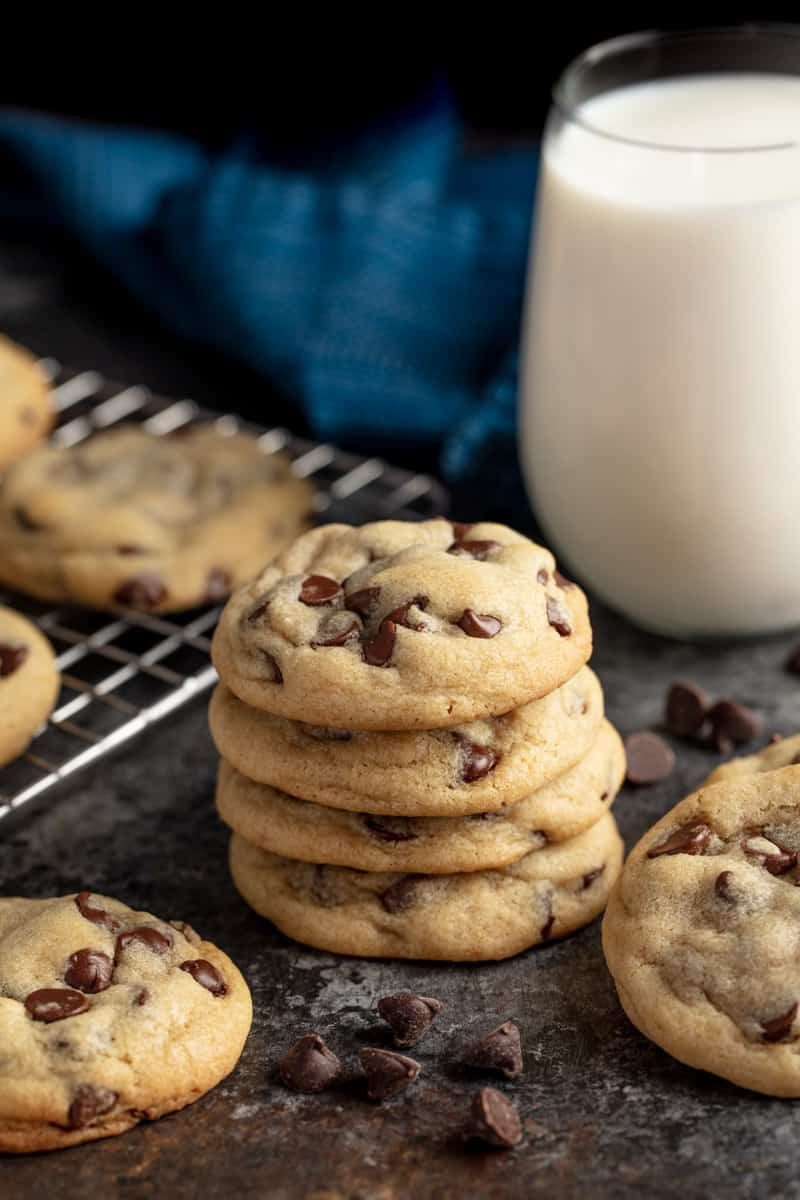 stack of chocolate chip cookies with a glass of milk in the background