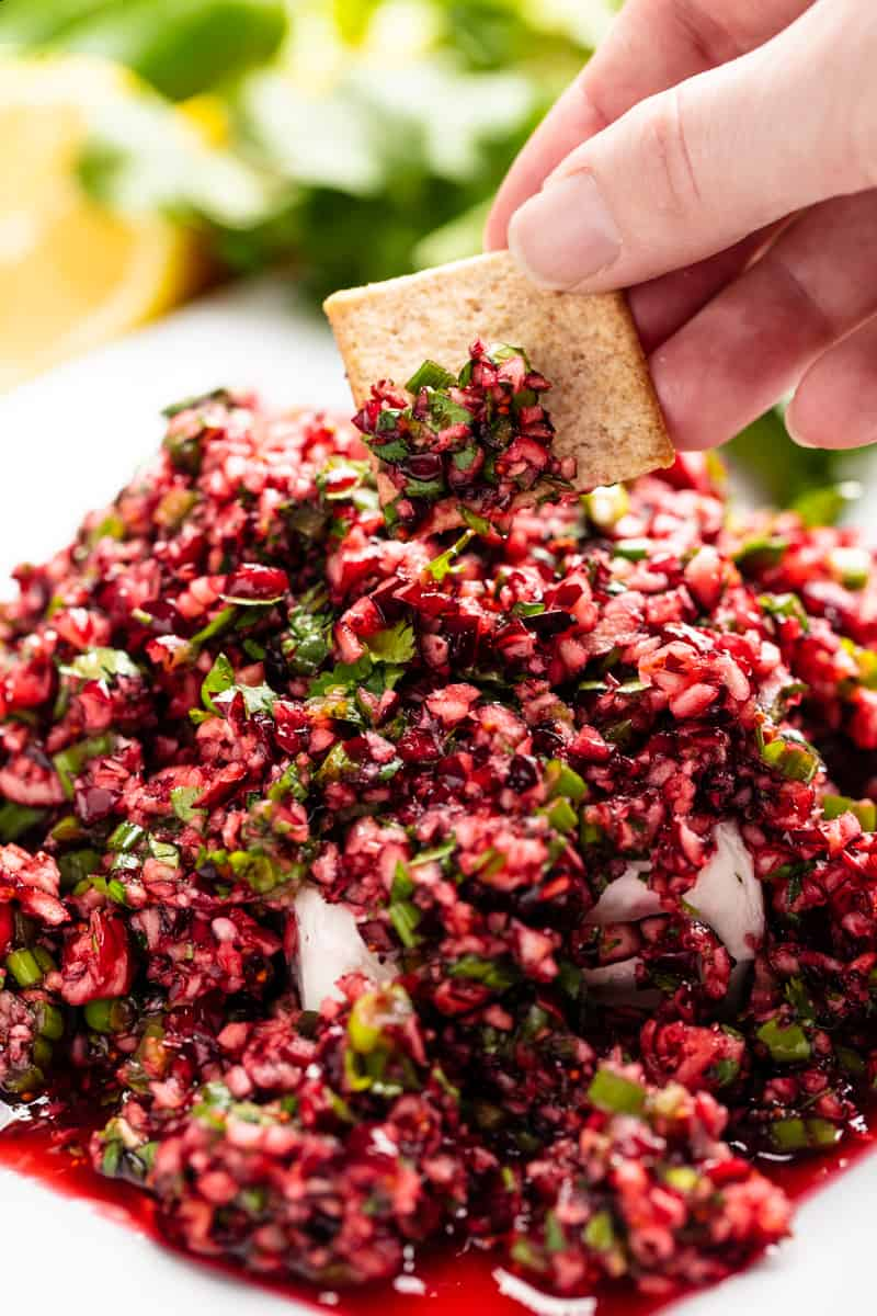Square cracker scooping some Cranberry Salsa on a white plate.