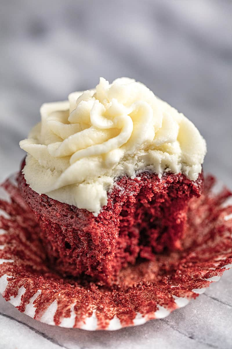 Red velvet cupcake with ermine frosting with a bite taken out of it