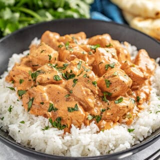 Butter chicken and white rice in black bowl