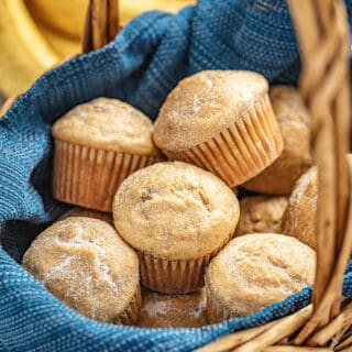 Banana muffins in a basket with bananas in the background