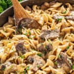 Beef stroganoff with sliced mushrooms on egg noodles stirred with a wooden spoon, parsley in background