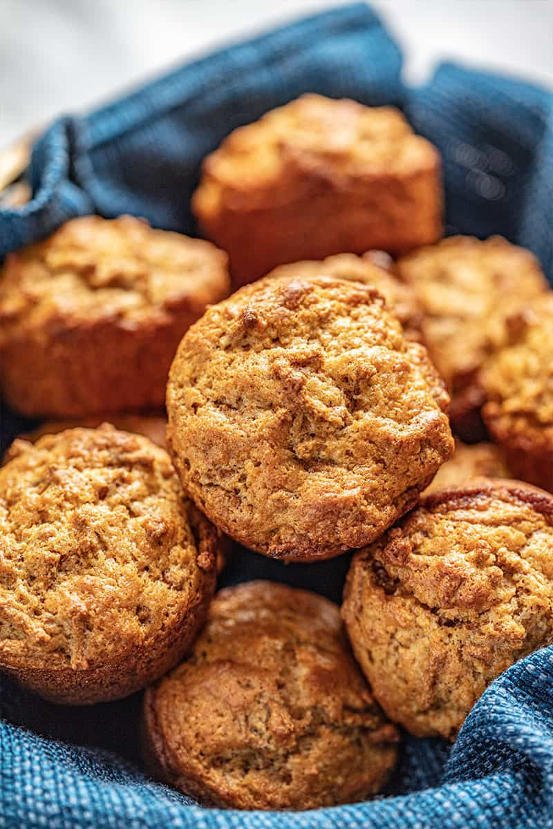 Bran muffins in a basket with a blue cloth.