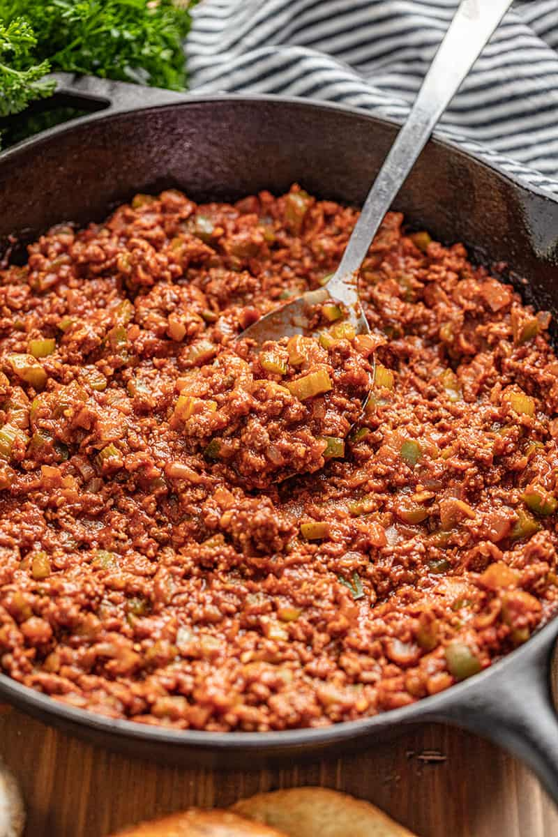 Sloppy Joe meat and veggie mix in skillet with spoon