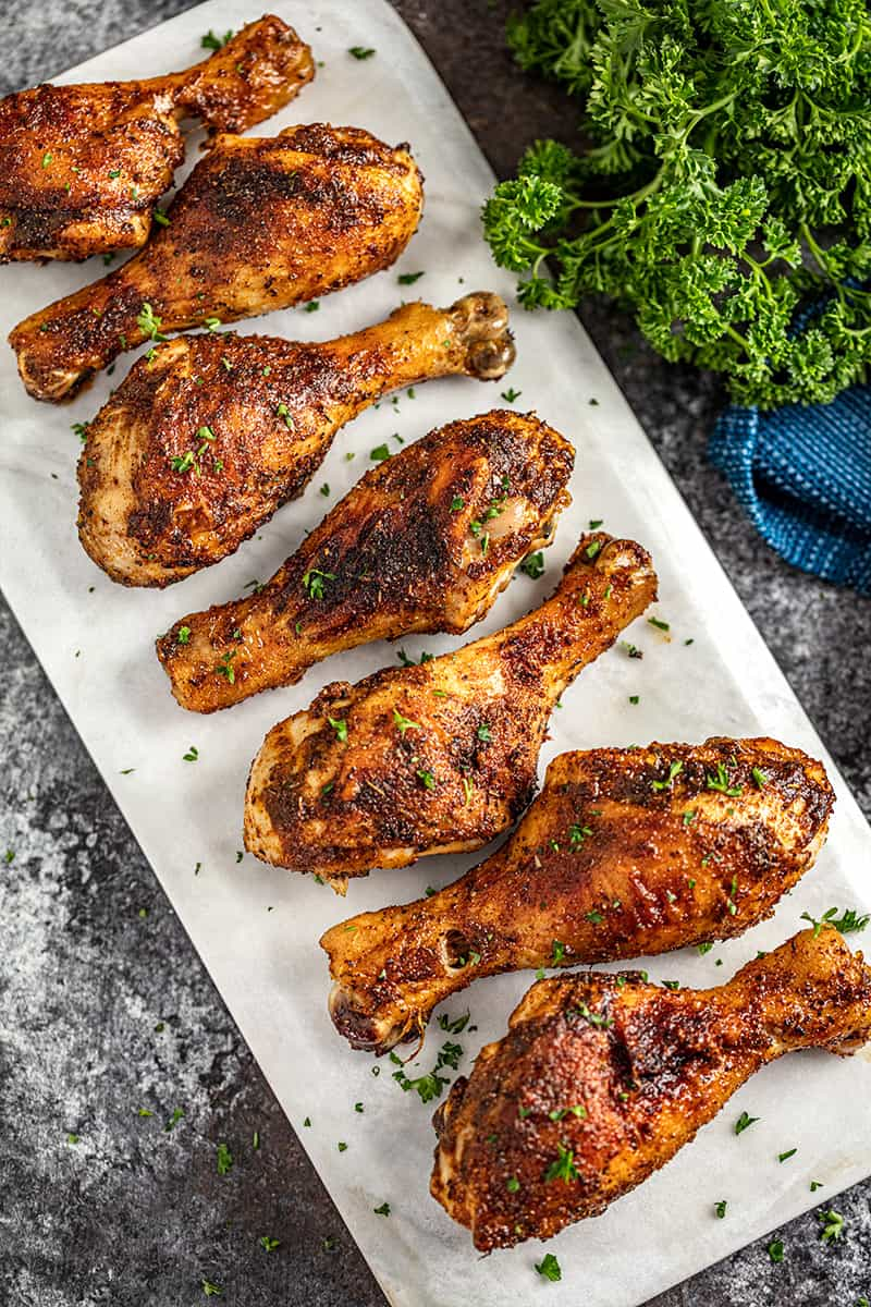 Cajun spiced chicken drumsticks lined up on a marble platter