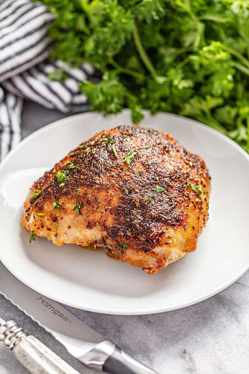 Crispy oven baked chicken thigh on white plate