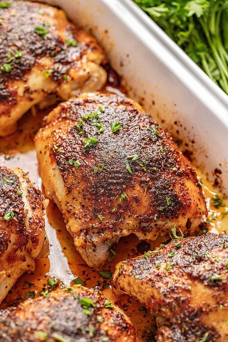 Baked Chicken Thighs in a baking dish topped with parsley and sitting in its own juices.