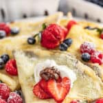 Easy crepes with strawberries and blueberries on plate.