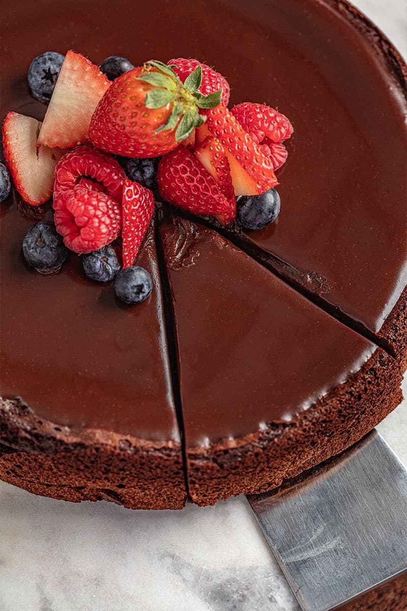 Bird's eye view of a flourless chocolate cake with a slice being taken out of it.
