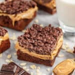 Peanut butter crunch brownies on tray with glass of milk and spoon of peanut butter