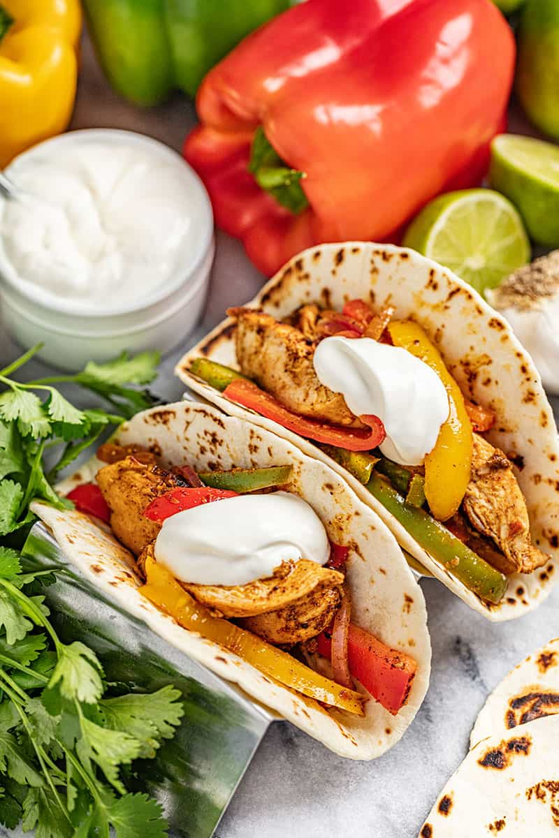 Chicken Fajitas in flour tortillas with multi colored bell peppers and onion and topped with sour cream