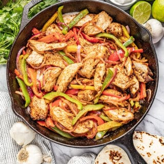 Chicken Fajitas in a cast iron skillet with multi colored bell peppers and onion