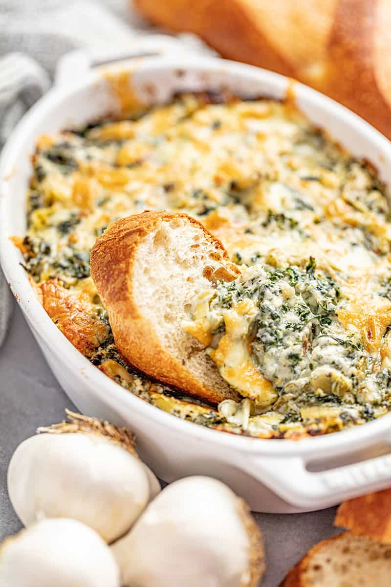 Bread dipped in spinach artichoke dip