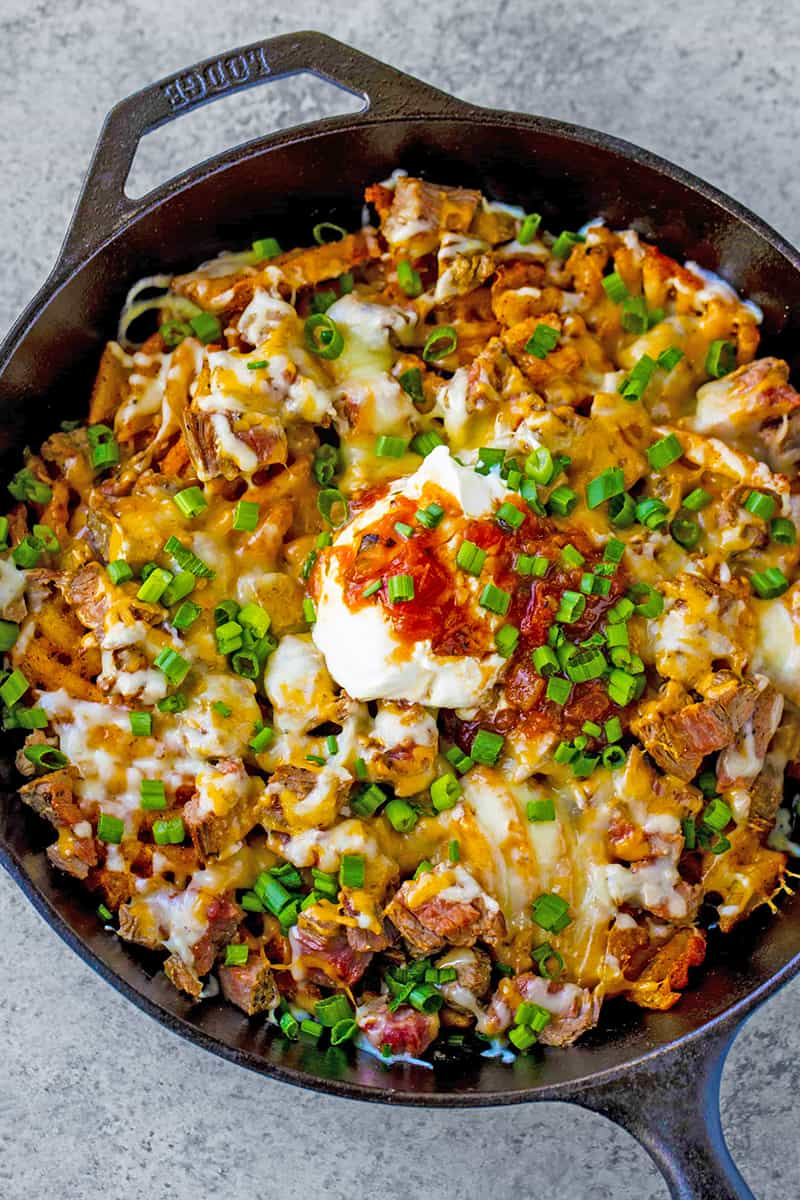 Bird's eye view of Close up of Steak and Potato Nachos in a skillet.
