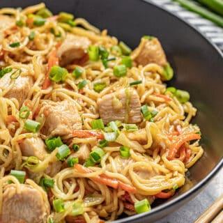 Chicken chow mein in a black bowl with chopsticks