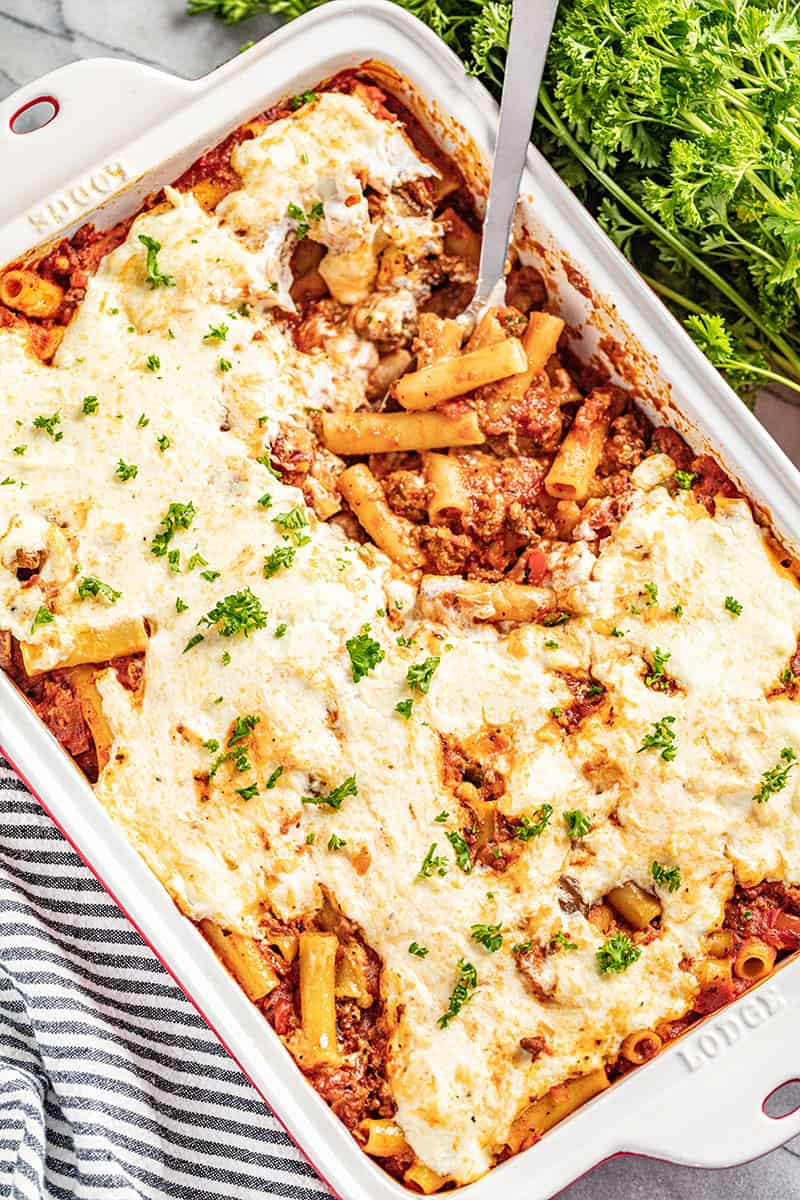 Baked ziti in a white deep baking dish with a spoon