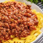 Bolognese sauce on white plate on bed of noodles