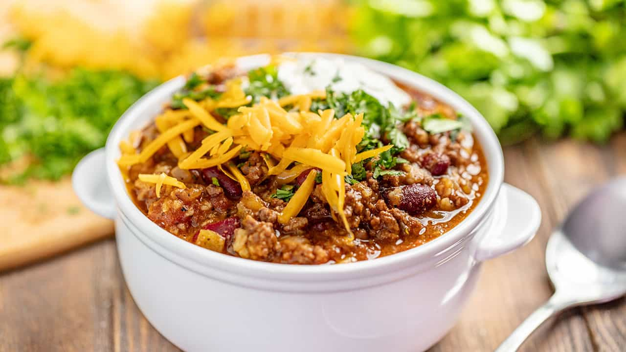 A cup of chili with cheese on top in white ceramic bowl