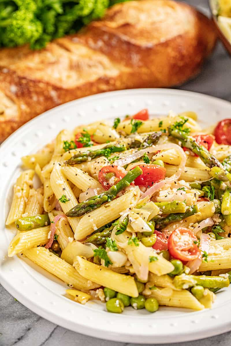 A serving of creamy pasta primavera on white plate