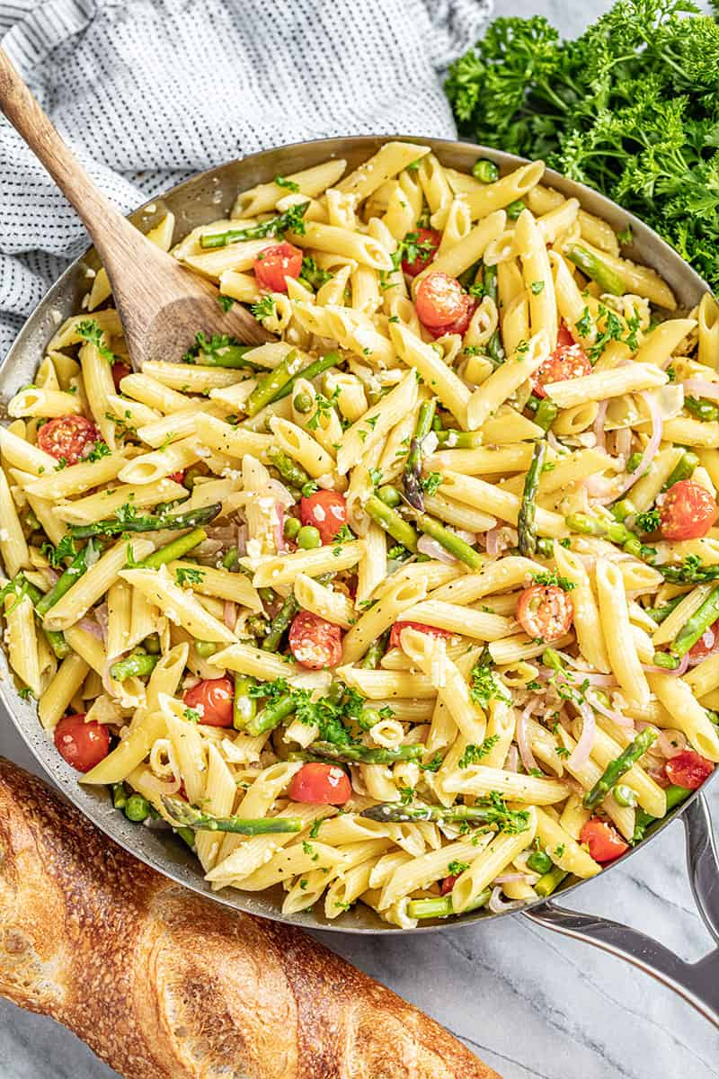 Creamy pasta primavera in skillet with wooden spoon