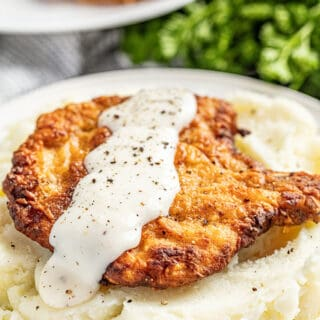 Crispy fried pork chop with gravy on bed of mashed potatoes