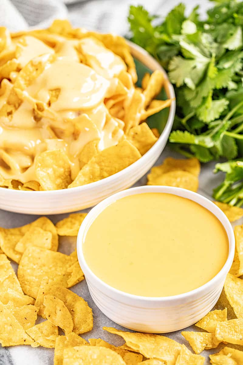 Bowl of nacho cheese sauce next to a bowl of chips with drizzled cheese sauce on top
