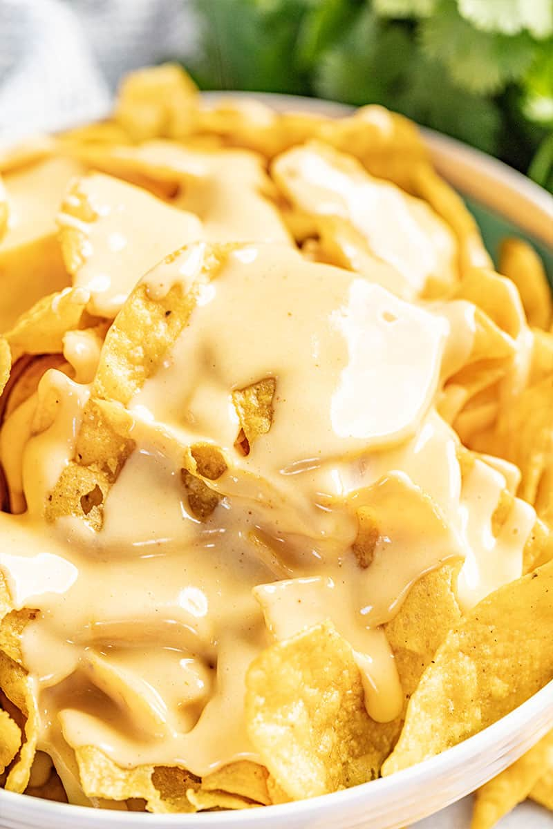 Bowl of chips coated with nacho cheese sauce