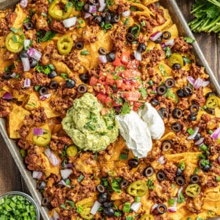 Nachos on a baking sheet with salsa and green onions on the side