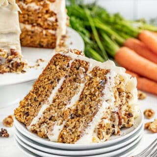 A slice of carrot cake on its side on a stack of white plates