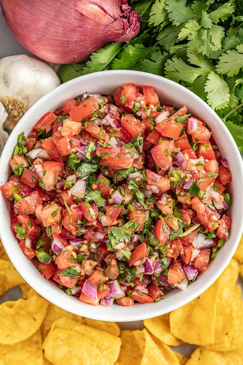 Overhead view of a white bowl filled with homemade salsa