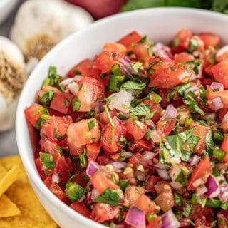 Homemade salsa in a bowl surrounded by chips and garlic