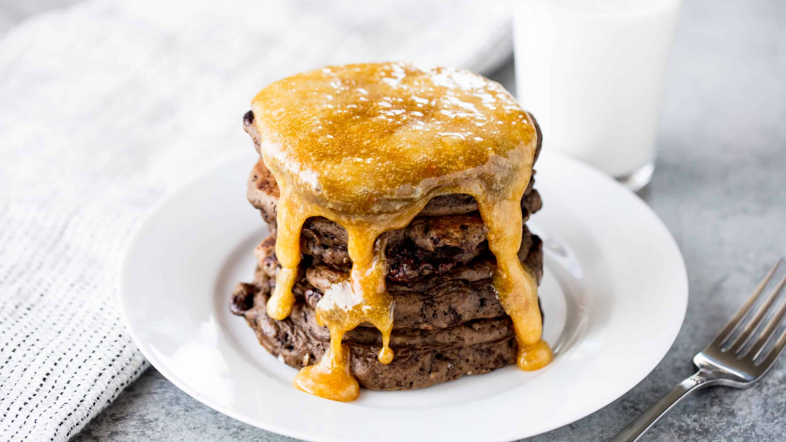 A stack of chocolate pancakes covered in a caramel syrup on a white plate.